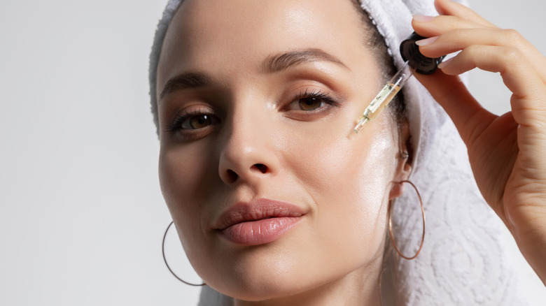Woman applying facial oil