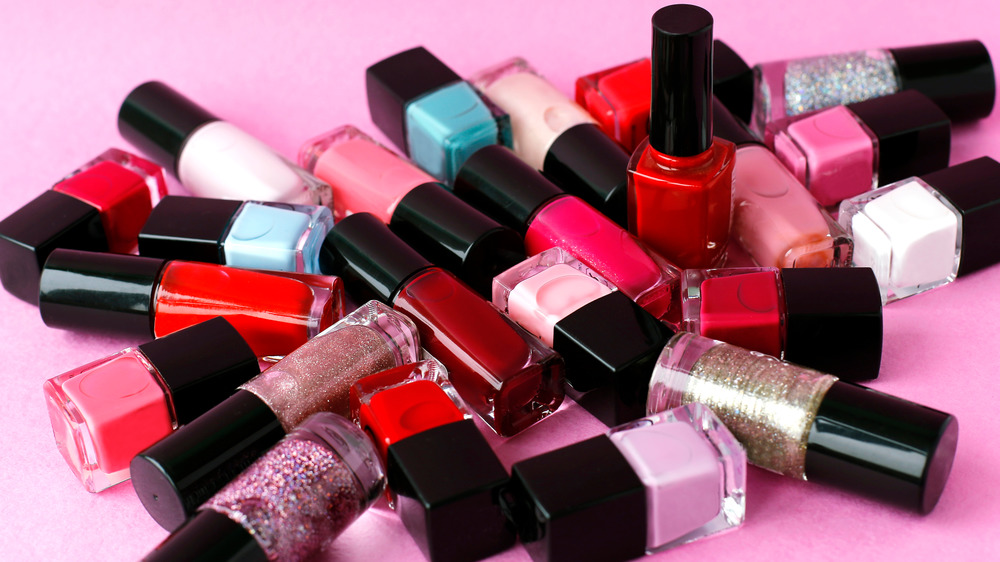 Several bottles of nail polish in a pile on a pink background.