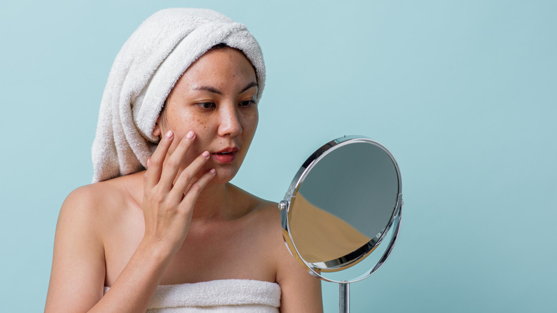 A woman touching the side of her face while looking at the mirror.
