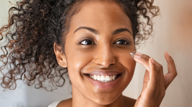 Woman appllying moisturizer to her face