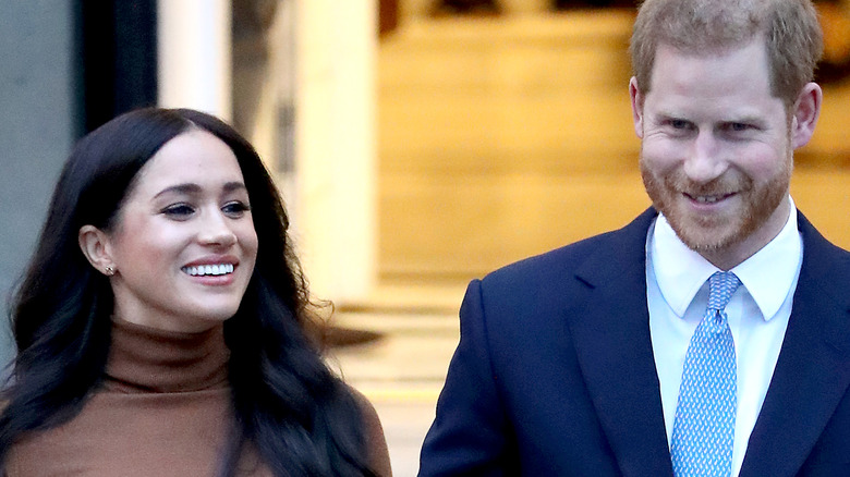 Meghan Markle and Prince Harry hold hands