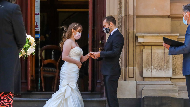 Masked couple getting married in microwedding