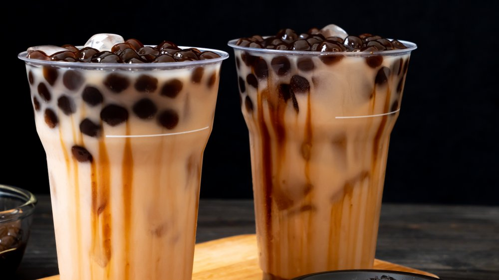 Two cups of bubble tea with syrup added