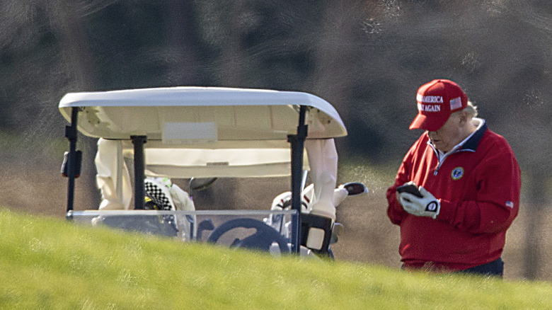 Donald Trump using his phone on the golf course