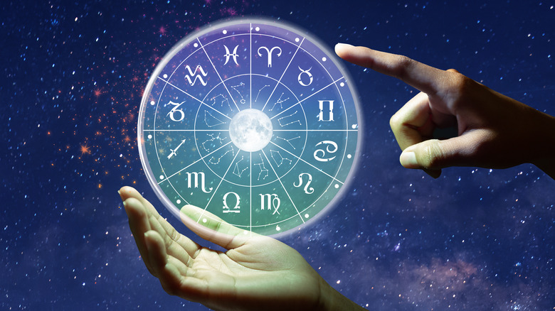 Hand pointing to a zodiac chart