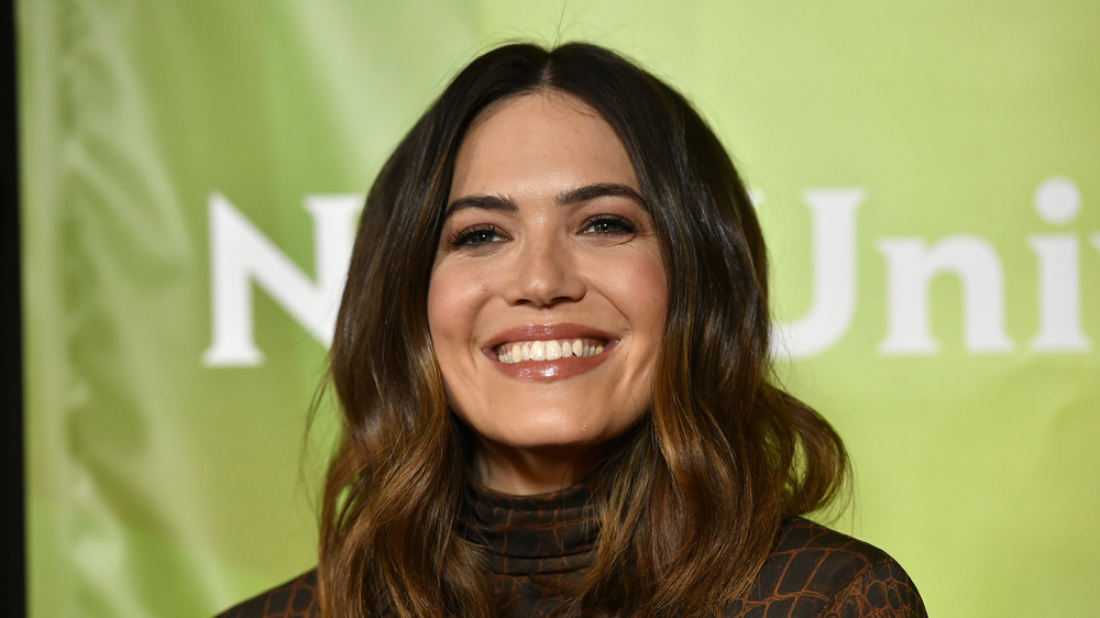 Mandy Moore smiling with green background