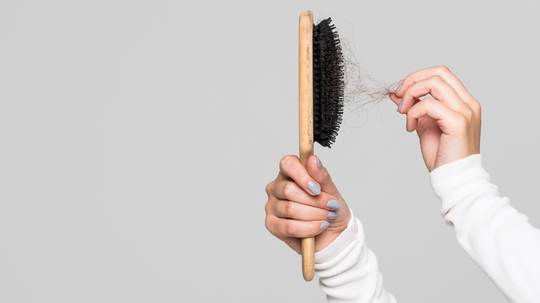 woman pulling an access amount of hair out of a brush
