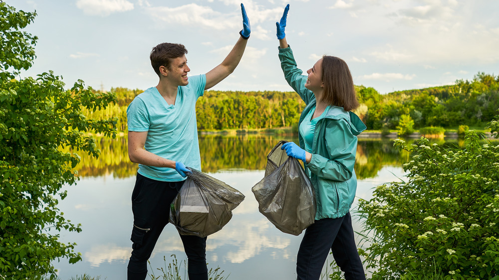 A man and woman high-five while holding trash bags