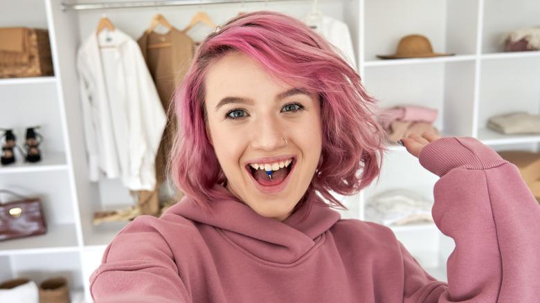 girl with pink hair, wearing pink hoodie, smiling
