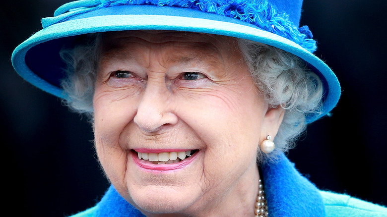 Queen Elizabeth smiling while wearing a blue suit