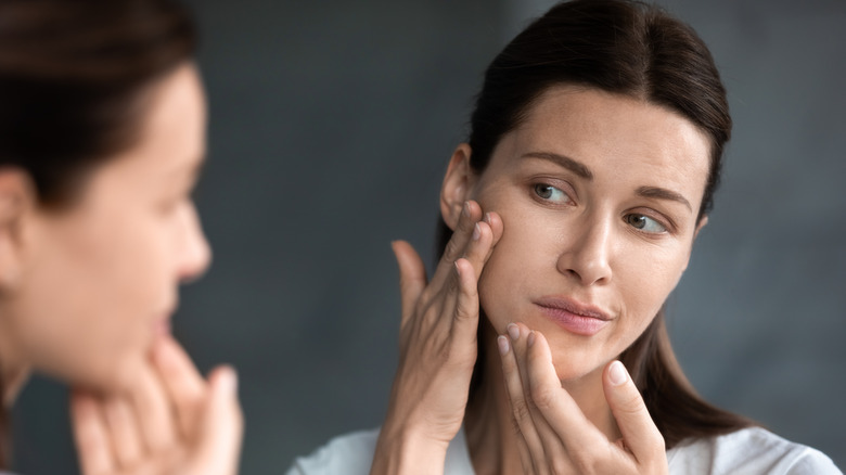 Woman examining dry skin in the mirror