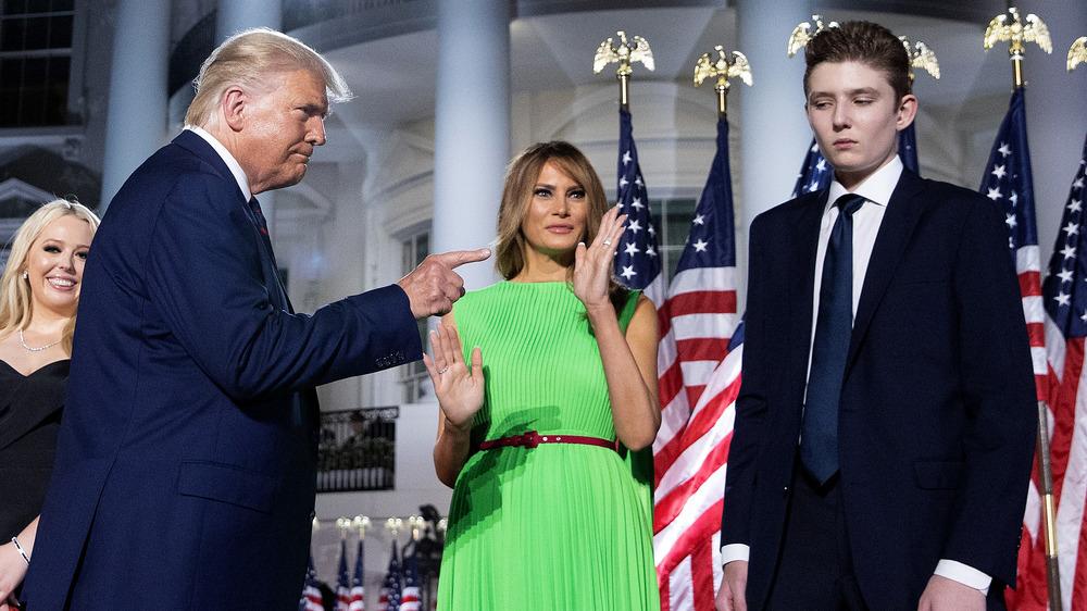 Barron Trump looking unhappy as President Trump points at him with Melania Trump