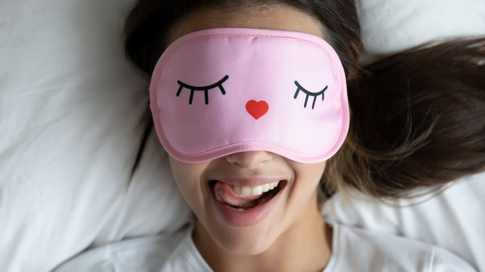 Woman wearing a pink sleep mask while lying on a white pillow and smiling.