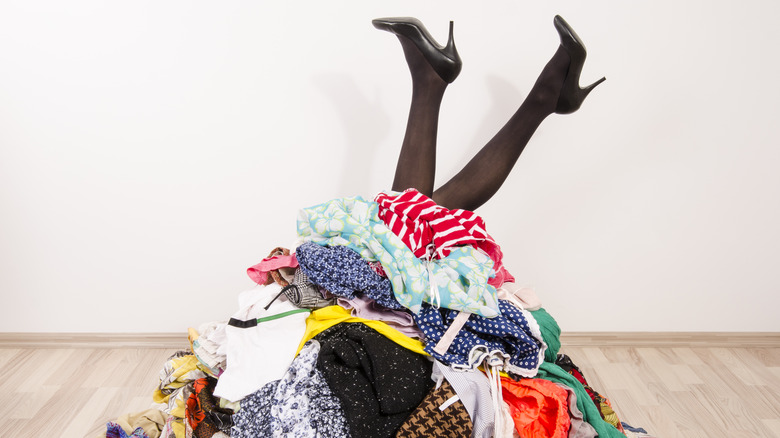 Messy pile of clothing with a woman's legs sticking out