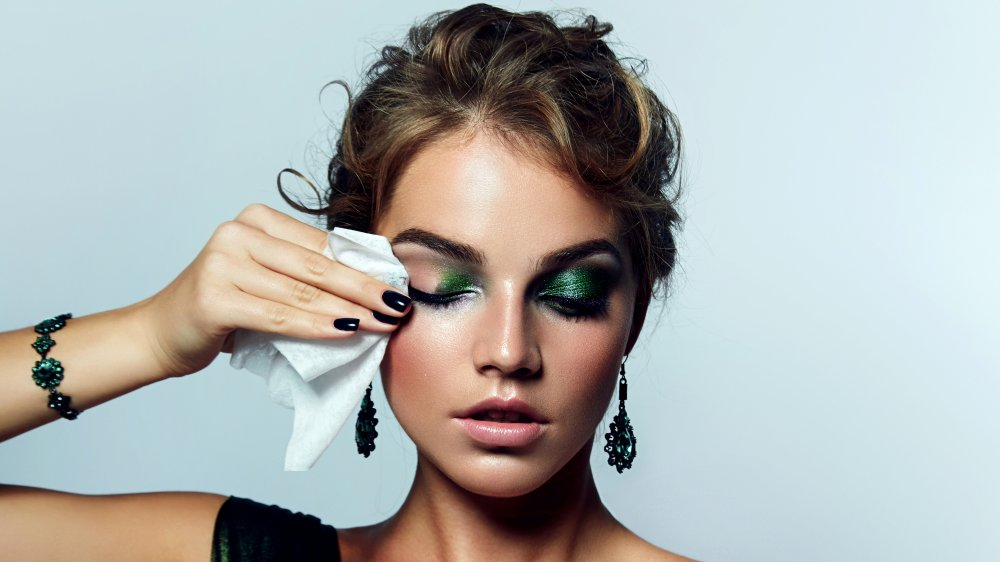 Woman using makeup remover wipe on green eye shadow
