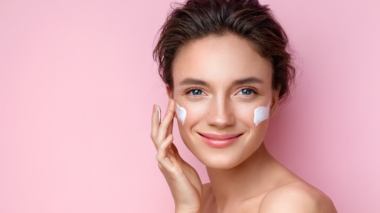 woman applying lotion to face