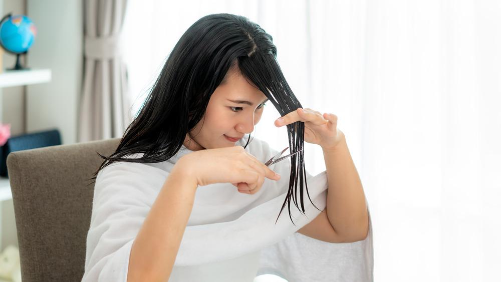 Woman cutting her bangs