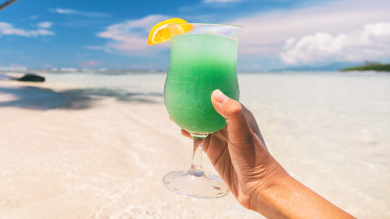 Hand holding up green drink on the beach
