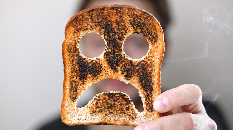 Woman holding a slice of burnt toast