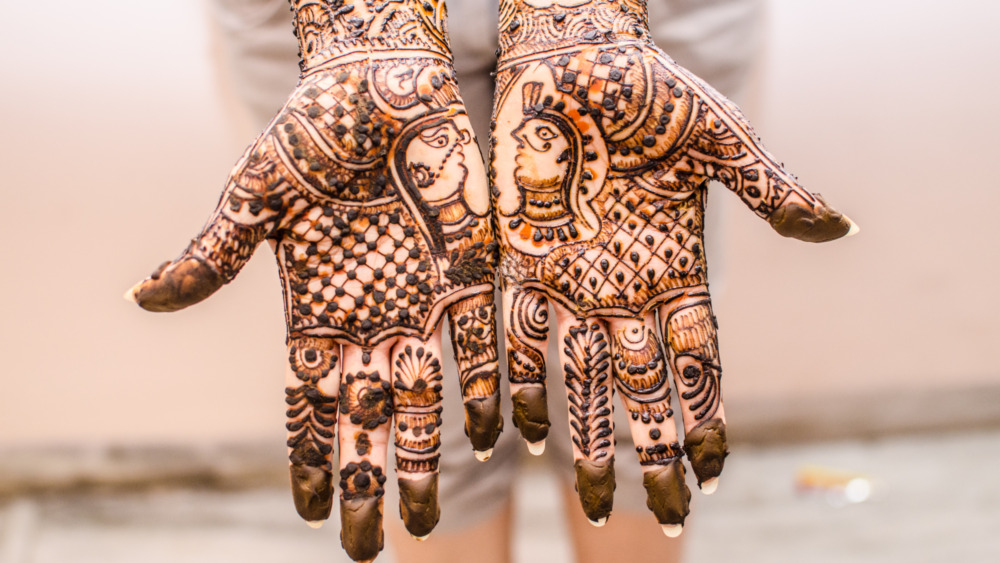 Two hands held palm out covered in an intricate design made with henna paste