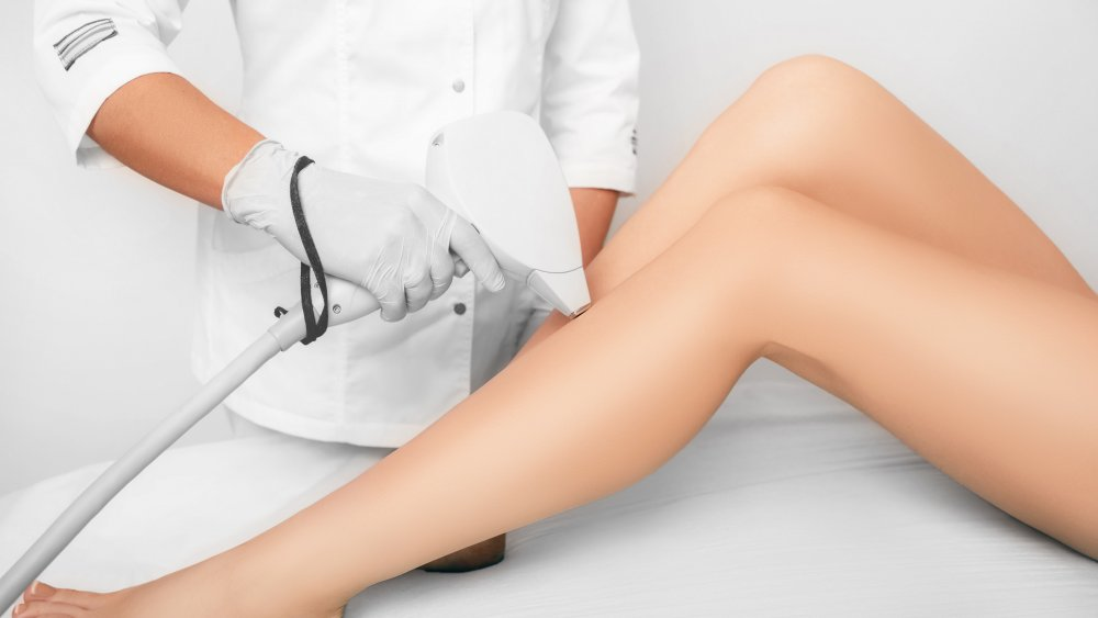 Legs and a laser hair remover in a practitioner's hand