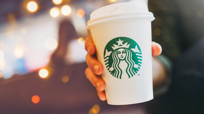 Person holding Starbucks cup