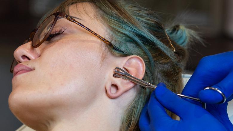Woman getting her ears pierced
