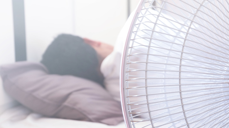 Person sleeping with a fan nearby