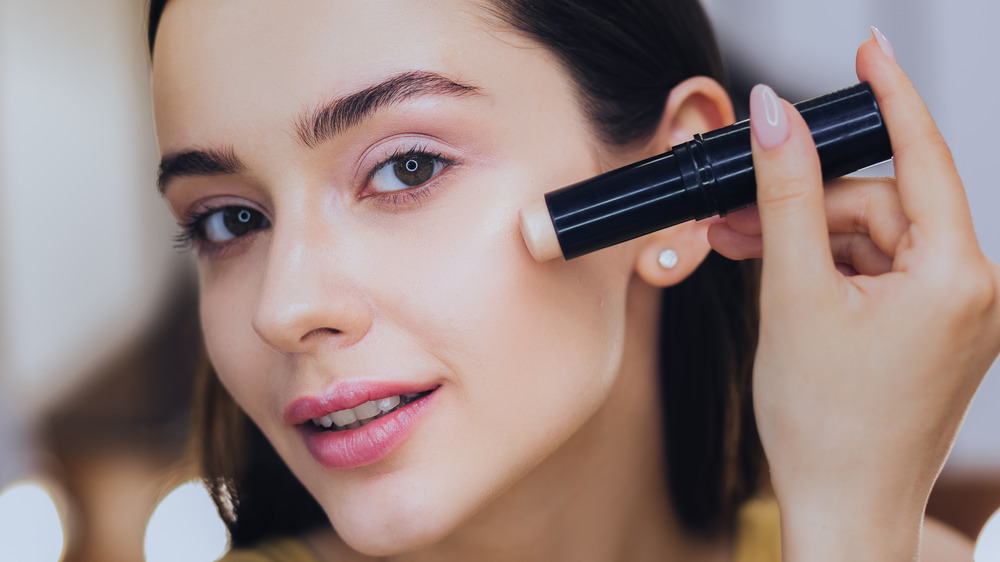 Woman applying stick foundation to face