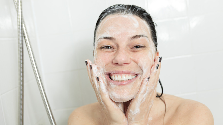 Woman washing face in shower