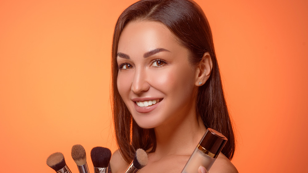 Woman holding foundation and brushes