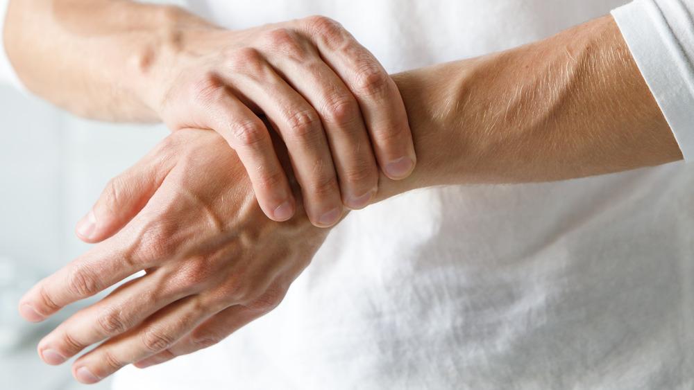 Person touching their wrist