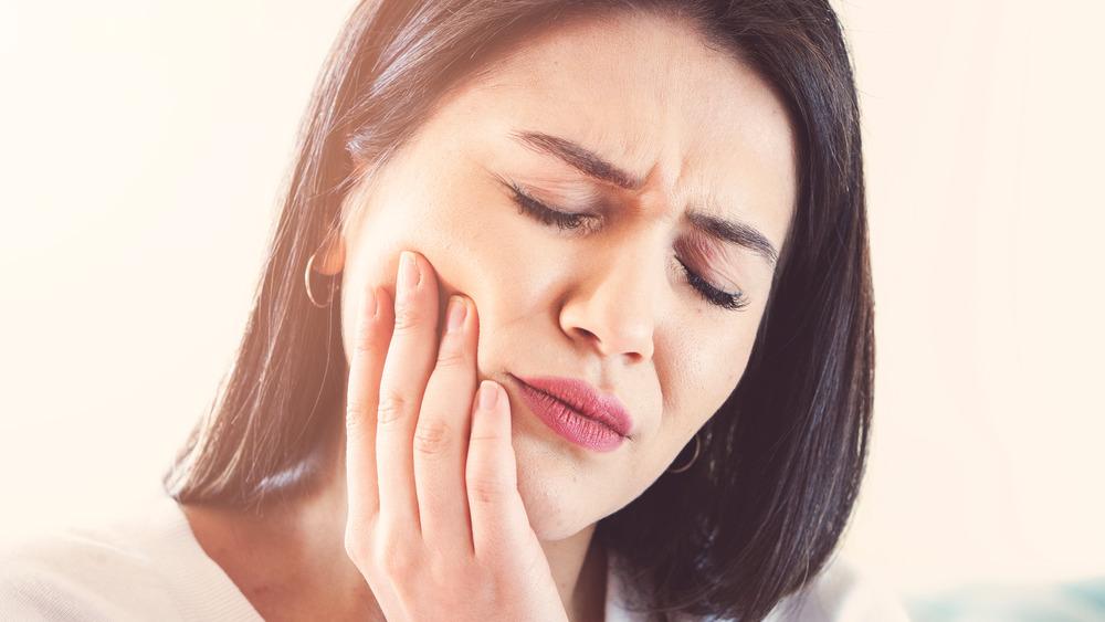 A woman in pain, touching her cheek