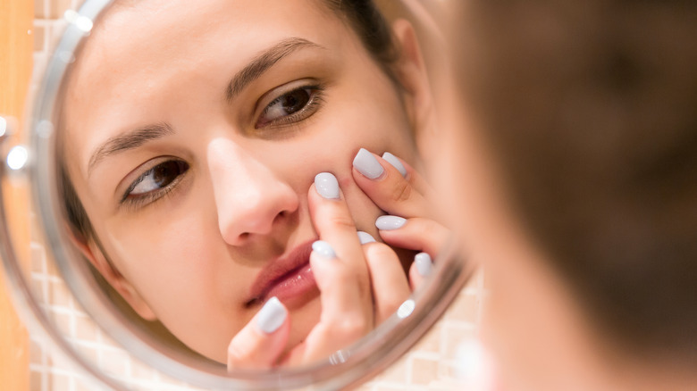 Girl squeezing pimple in mirror