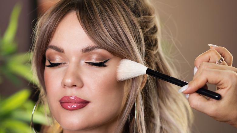 applying makeup on cheekbones