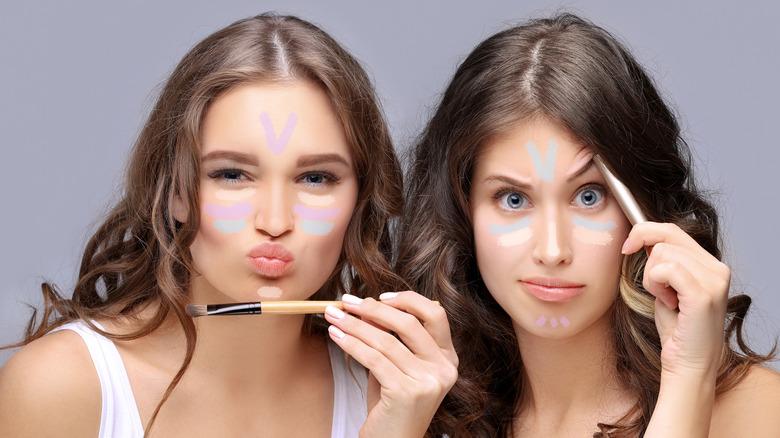 Two women applying makeup