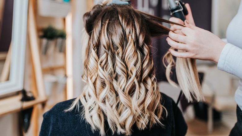 Woman having her highlighted hair styled at the salon