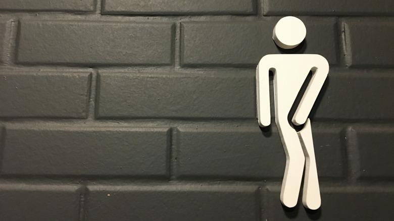 bathroom symbol holding it