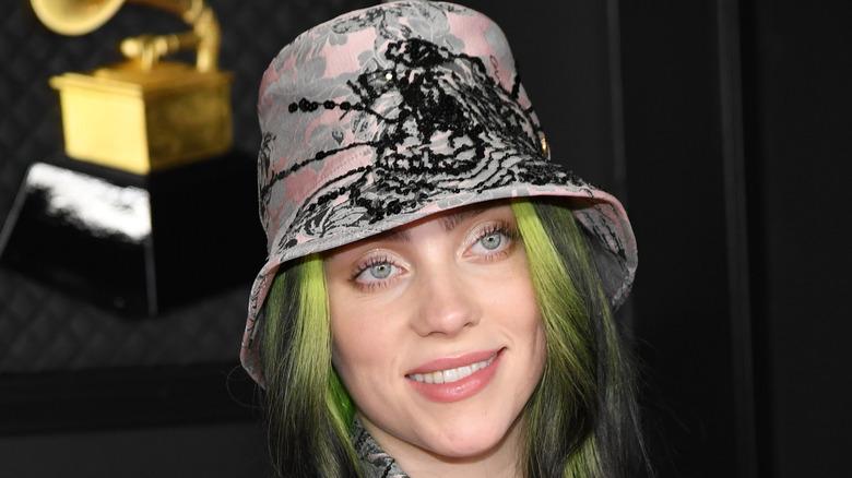Billie Eilish rocks a bucket hat while holding her Grammys.