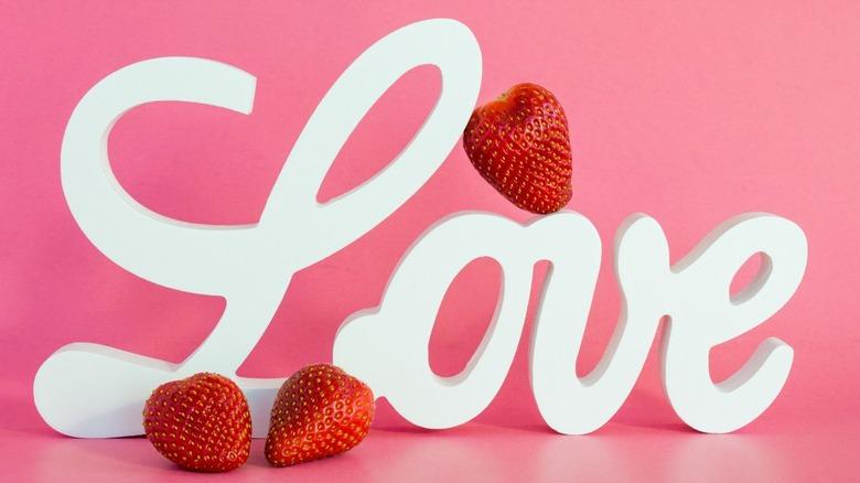 """Love"" written in white, pink background, strawberries"
