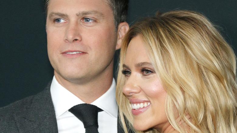 Colin Jost and Scarlett Johansson smiling at a premiere