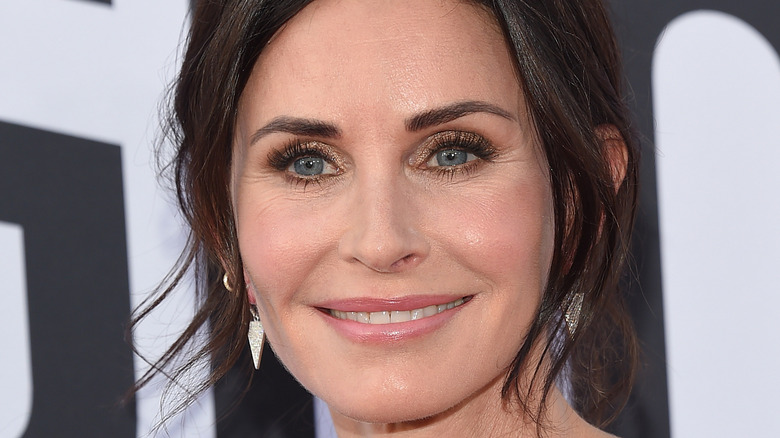 Courteney Cox smiling with her hair up
