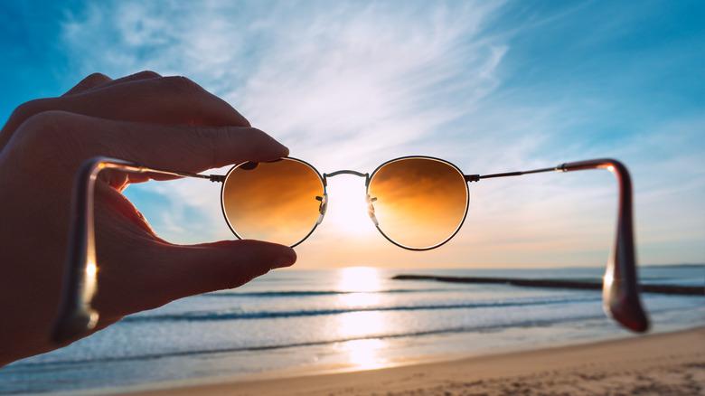 hand holding sunglasses to sun