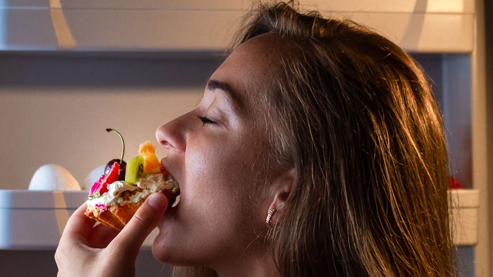 Young woman eating cake before bed