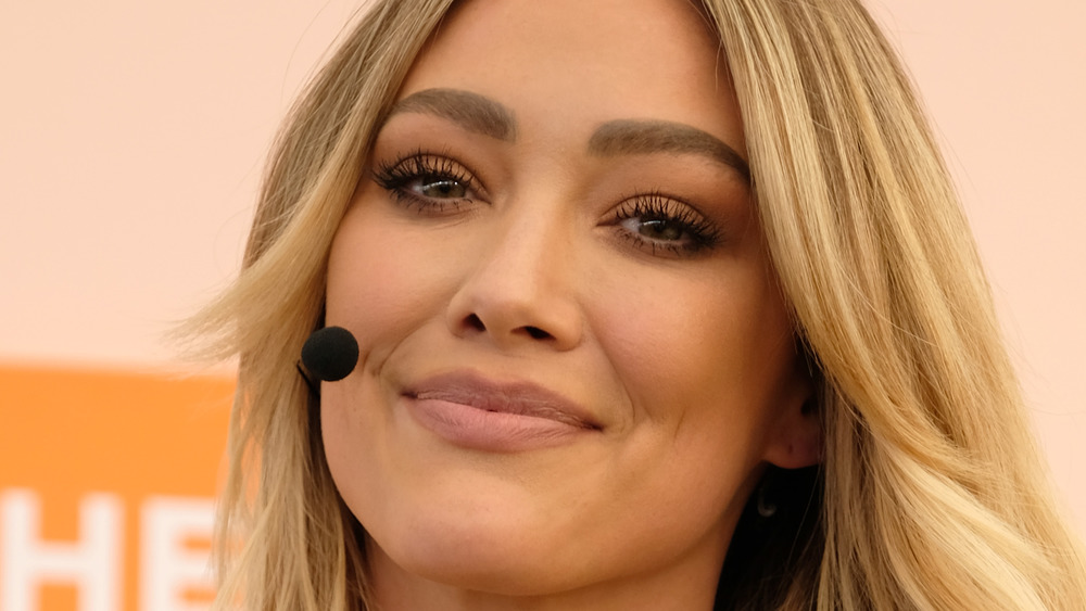 Hilary Duff smiling with microphone