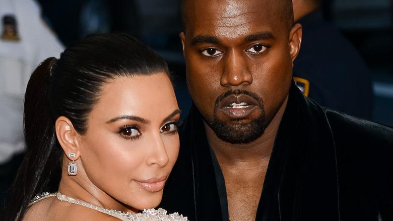 Kim Kardashian and Kanye West pose for the camera.