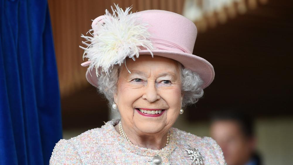 Queen Elizabeth II smiling in a pink hat