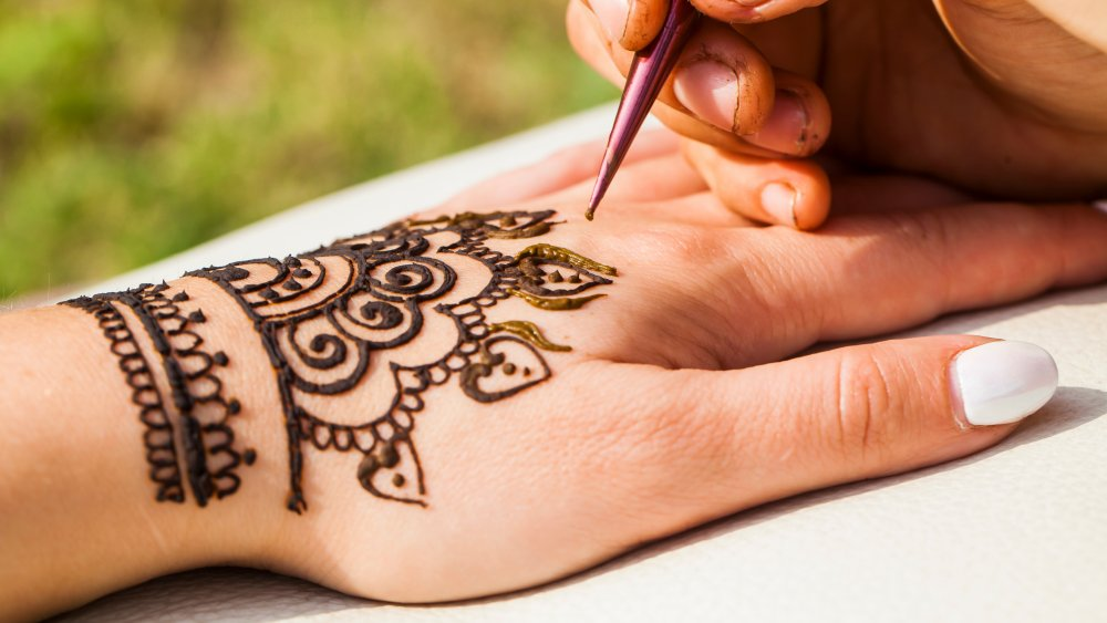 Woman getting a henna tattoo done