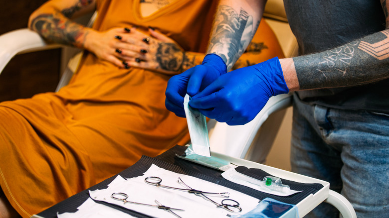 person sitting in tattoo and piercing shop