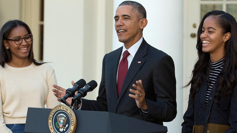 Malia, Sasha, and Barack Obama smiling